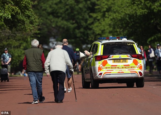 Pictured: an elderly couple drives past a police patrol car in Greenwich Park, London on May 2