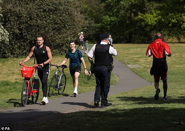 Pictured: police officer with megaphone asks people to continue moving around Greenwich Park, London, as the UK continues to lock in to curb the spread of coronavirus