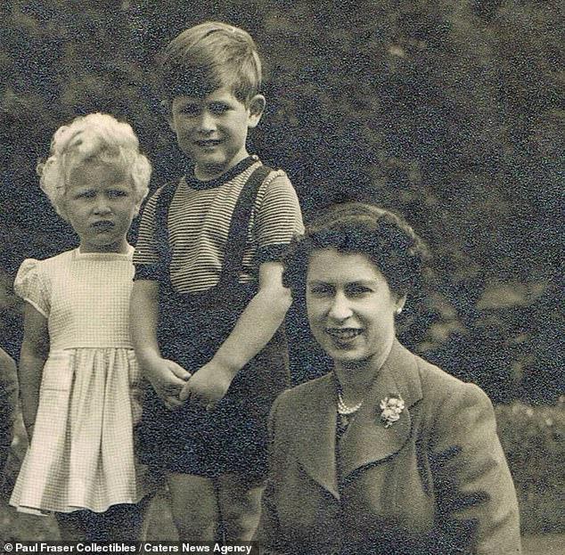 La reine aurait eu environ 28 ans en 1954 lorsque l'image festive a été prise. Une princesse Anne aux cheveux blonds, alors âgée de deux ans, est vue à côté de son frère aîné, le prince Charles, alors âgé de cinq ans.