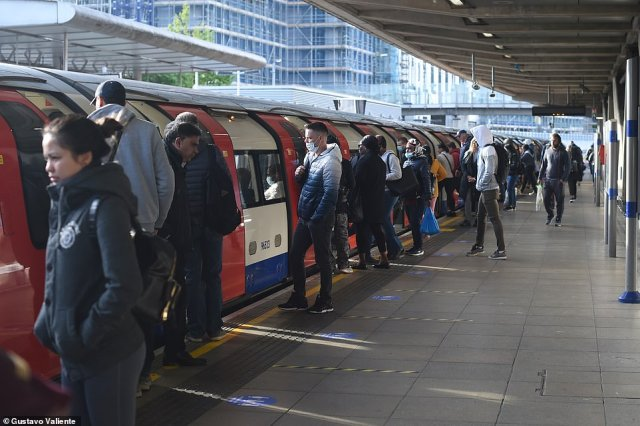Commuters board the Tube at Canning town this morning