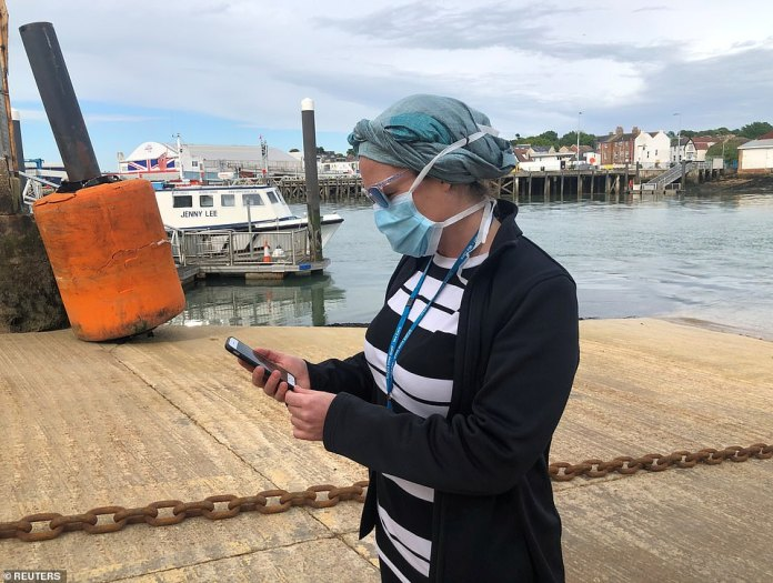 NHS worker Anni Adams watches the new NHS app on her phone on the Isle of Wight today