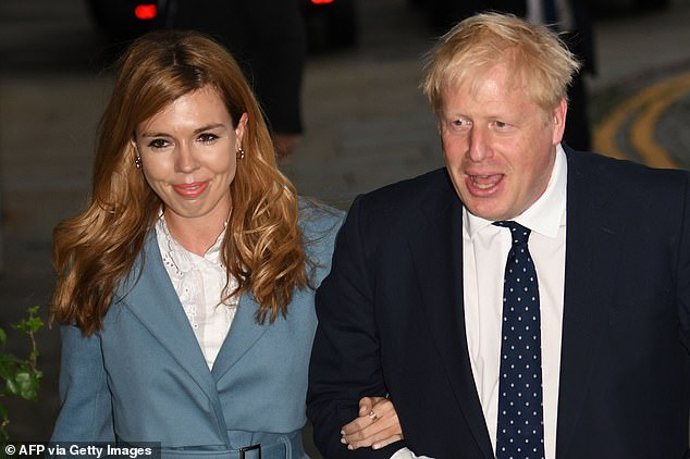 Pictured: British Prime Minister Boris Johnson walking with partner Carrie Symonds