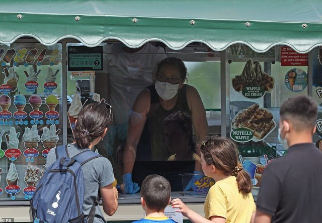 An ice cream seller takes orders from behind a plastic screen while wearing a face mask as crowds line up behind customers