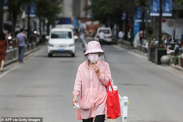 Wuhan has reported five new confirmed cases, all living in the same residential complex. In the photo, a woman wears a face shield as she walks a street in Wuhan on Monday