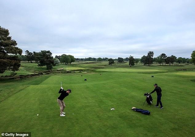 Charlie Steadman, member of Walton Heath Golf Club, kicks the second hole on the new course at Tadworth, Surrey