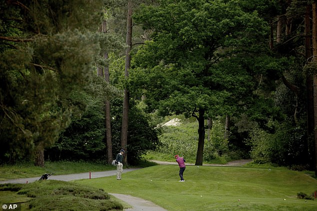 A golfer hits a tee after the reopening of Sunningdale Golf Club in Berkshire this morning