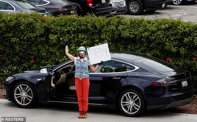 A woman is pictured outside the Tesla factory wearing a mask with Elon Musk's face on in, holding a sign that reads 'thank you for wearing your Musk'