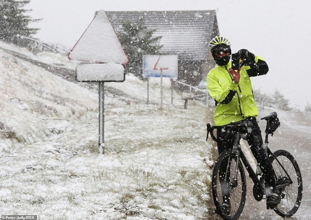 A cyclist stops to take a picture of the snow during on the A939 today as snow blizzards hit the Highlands on Tuesday