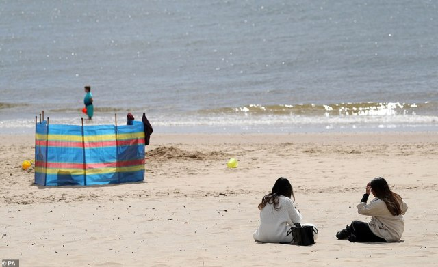 Warmer weather is returning to Britain, with the remainder of May posed to be sunny and relatively rain free. Pictured:People sit down on Bournemouth beach in Dorset on the first day of easing for some coronavirus lockdown restrictions
