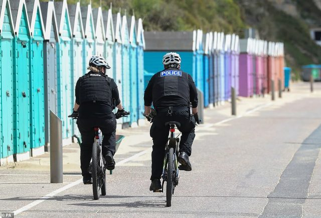 Police officers on bicycles patrol Bournemouth beach in Dorset as warmer weather starts to return to Britain