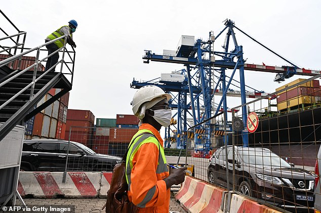 Workers look on as containers are offloaded from a ship at the Abidjan-terminal at the port of Abidjan, Côte d'Ivoire