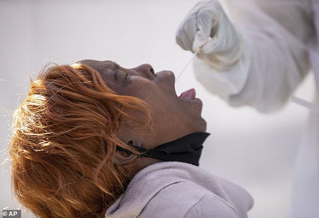 A woman opens her mouth for a heath worker to collect a sample for coronavirus testing during the screening and testing campaign aimed to combat the spread of COVID-19 at Alexandra township in Johannesburg, South Africa