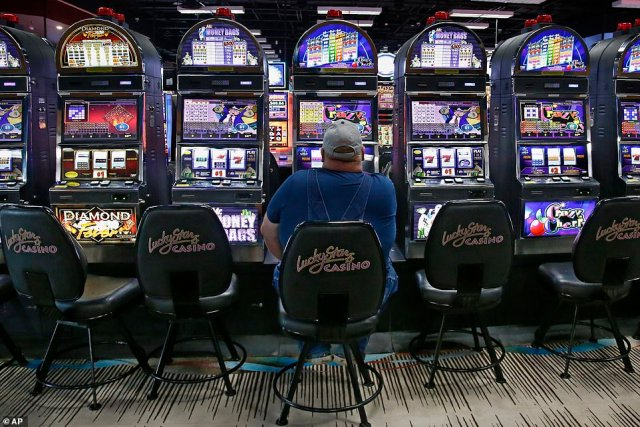 Some casinos, which are usually 24-hour operations, now have limited hours. Pictured: A man plays on a gaming machine at Lucky Star Casino, May 15
