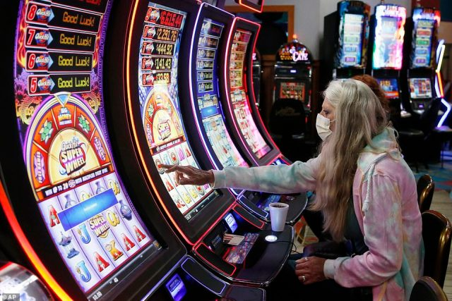 To maintain social distancing at slot machines, whenever a customer sits down at a machine at Lucky Star, the two on either side will disable. Pictured: Debbie Blanchard, of El Reno, Oklahoma, plays on a gaming machine at Lucky Star Casino, May 15
