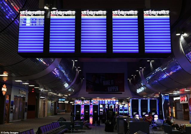 But Democratic Gov Steve Sisolak has said gambling venues will not be among businesses restarting activities during the first phase of Nevada's reopening. Pictured: Flight board monitors above a closed gaming area at McCarran International Airport