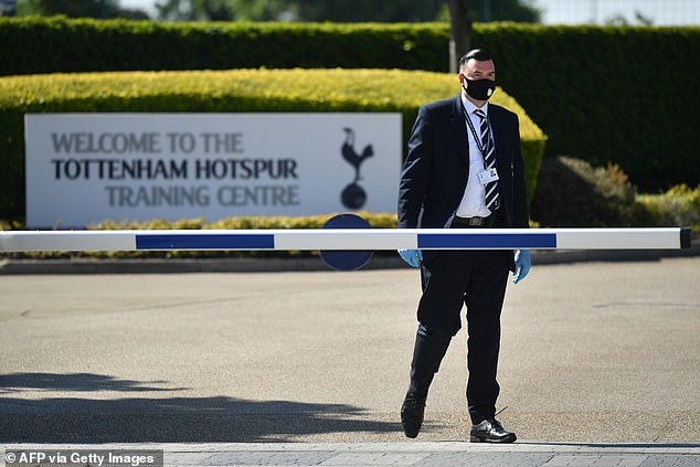 Security guard patrols the entrance to Tottenham training ground with a face mask