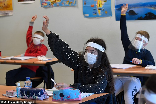 FRANCE: Schoolchildren wearing protective mouth masks and face shields attend a course in a classroom at Claude Debussy college in Angers, western France, on May 18, 2020