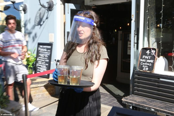 A woman wears a face visor as she carries a tray of drinks at The Althorp in Wandsworth Common as temperatures beings to rise