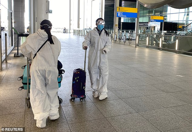 Passengers wearing protective clothing are seen at Heathrow Airport, London, today