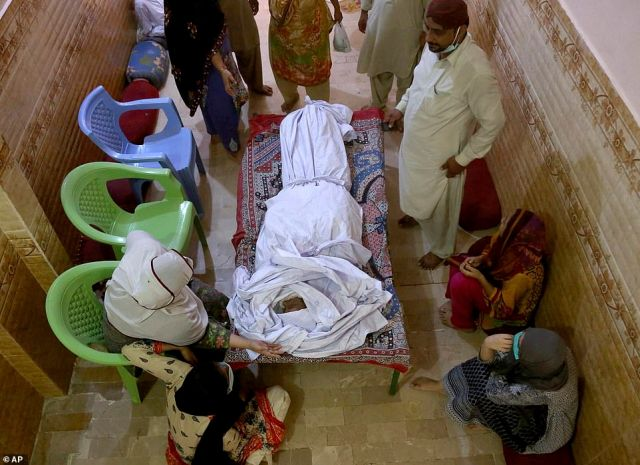 People mourn around the body of their relative, who was killed in the Friday's plane crash, at a morgue in Karachi, Pakistan, today. An aviation official says a passenger plane belonging to state-run Pakistan International Airlines carrying passengers and crew has crashed near the southern port city of Karachi
