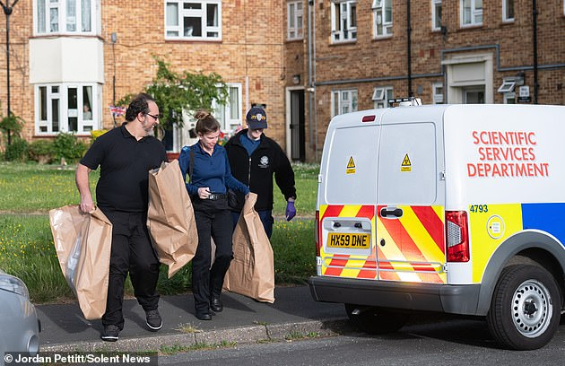 Pictured: Police carry out bagged items from a home in Leigh Park, Hampshire