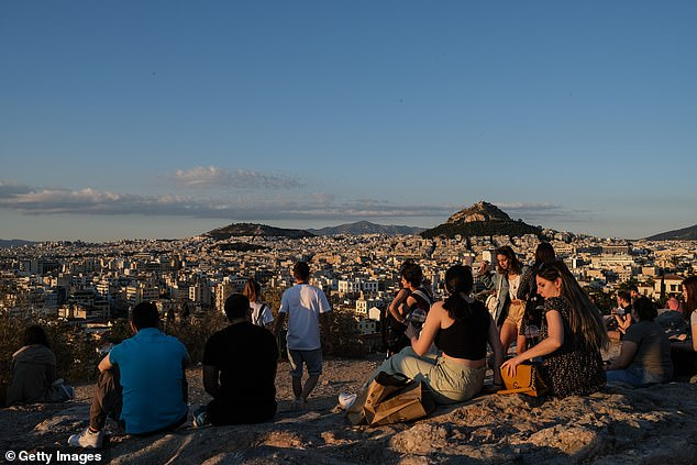 Tourists and local Athenians watch the sunset on Areopagus Hill, with the Lycabettus Hill in the background, on Saturday evening, above and below