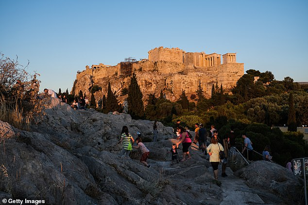Locals climb the Areopagus Hill with the Acropolis in the background to watch the sunset