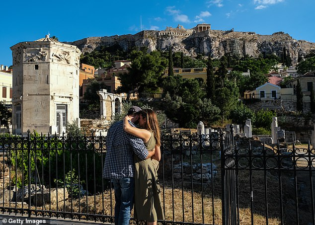 A couple shares a tender moment near the Tower of the Winds historical landmark, as tourists and locals stroll through the Monastiraki neighborhood on May 23