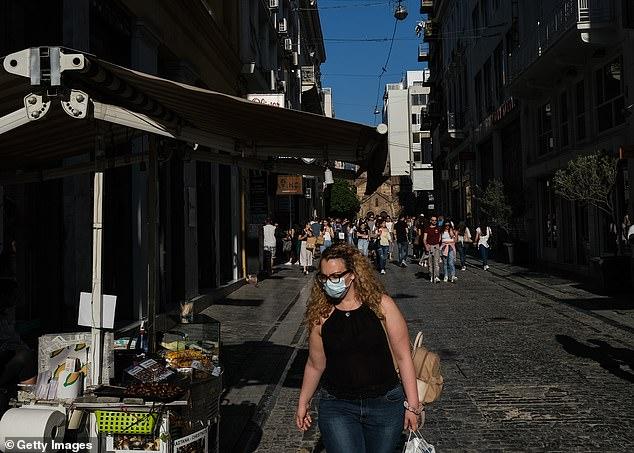 People stroll through the Monastiraki neighborhood on May 23 in Athens, Greece, above and below