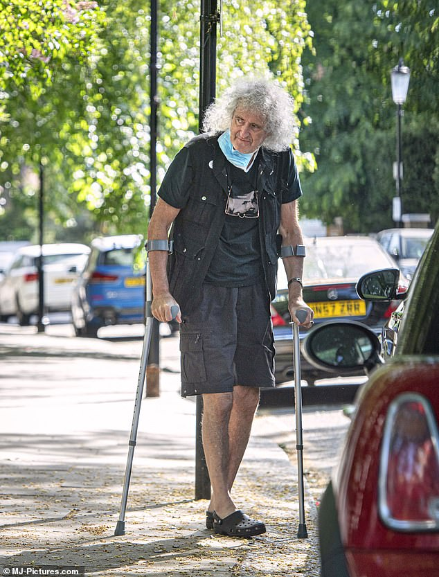 Crutches: Queen guitarist Brian May took his first steps after tearing his gluteus maximus - an injury that prevented him from walking unassisted