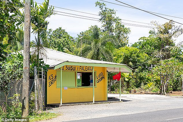 The island's capital city of Apia was turned to a ghost town with roads, schools and shops closed (pictured, a red flag hangs outside a cafe)