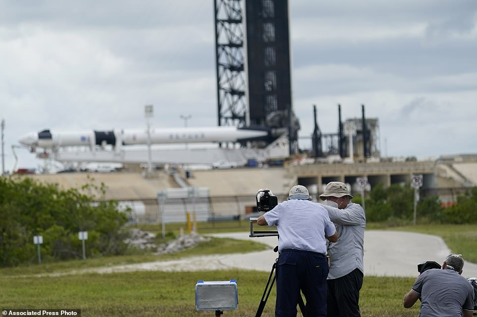 Photographers set up remote cameras as the SpaceX Falcon 9, with the Dragon crew capsule, is serviced on Launch Pad 39-A on Tuesday at the Kennedy Space Center in Cape Canaveral, Florida