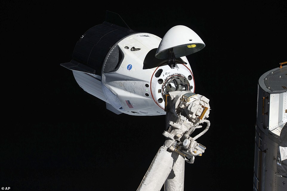 The uncrewed SpaceX Crew Dragon spacecraft, with its nose cone open to expose the docking mechanism, approaches the International Space Station's Harmony module