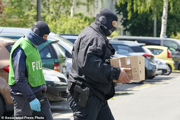 Federal police officers carry a box with secured documents during raids in Leipzig, Germany, Wednesday, May 27, 2020. Police in Germany have raided dozens of homes linked to anti-government groups suspected of manufacturing fake documents