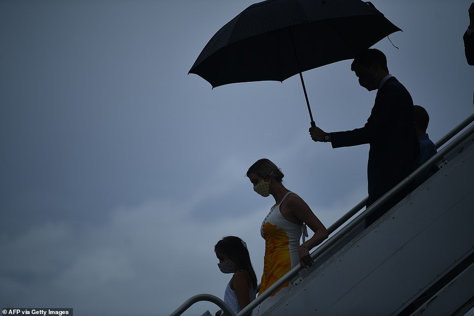 Jared Kushner holds out an umbrella for Ivanka Trump and their two kids as the Trump family arrives at the Kennedy Space Center in Florida