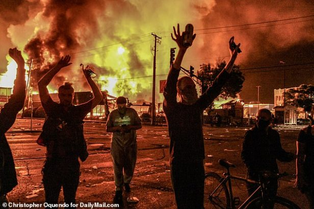 Minneapolis Department Police Chief John Elder confirmed in a midnight press conference that one person was shot and killed and that another person was being held in custody. Pictured: Scores of people were seen in the streets as fires raged around them amid conflicts with police