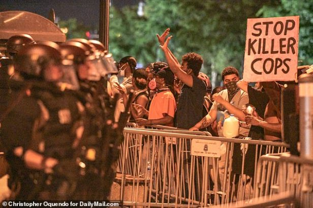 Protesters held placards aloft as they came up against police. One read 'stop killer cops'