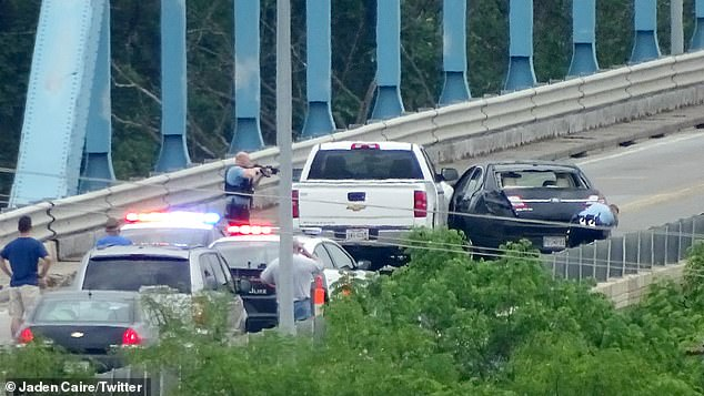 Royer's white Chevy Silverado is seen pushed up against the suspect's black car on the bridge on Wednesday morning