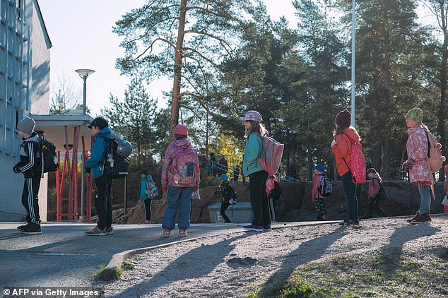 FINLAND: Pupils keep the social distances before entering Eestinkallio primary school, as it re-opens after lockdown measures were eased across Finland