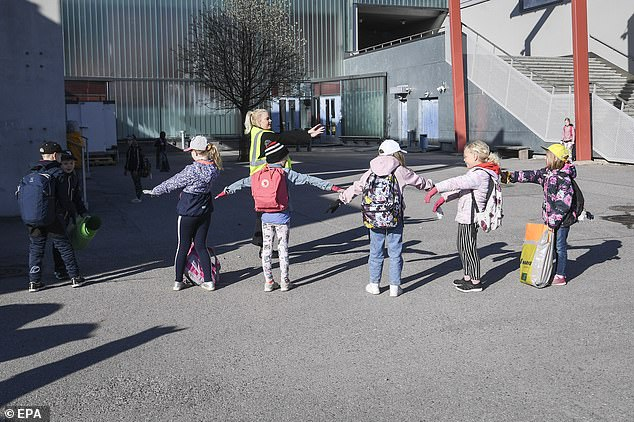 FINLAND: Students - some of whom are wearing gloves to prevent against coronavirus - are shown how to properly socially distance from one-another