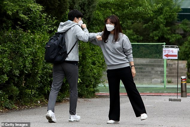 A teacher (right) welcomes a student back to school with an elbow bump at Kyungbock high school on May 20, 2020 in Seoul, South Korea