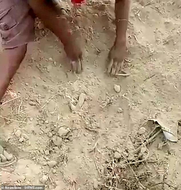 Child's tiny leg is seen coming out of the ground as an adult desperately tries to dig around his body