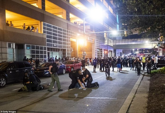 Detroit: Police detain and arrest protesters during a series of confrontations in the Michigan city last night