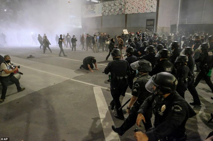 Police officers move forward to clear the street during a protest over the death of George Floyd in Los Angeles last night