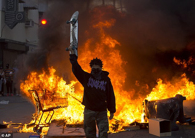 Minneapolis wasn't the only city where rioters took to the streets. Here a protester stands in front of a street fire in Los Angeles on Saturday