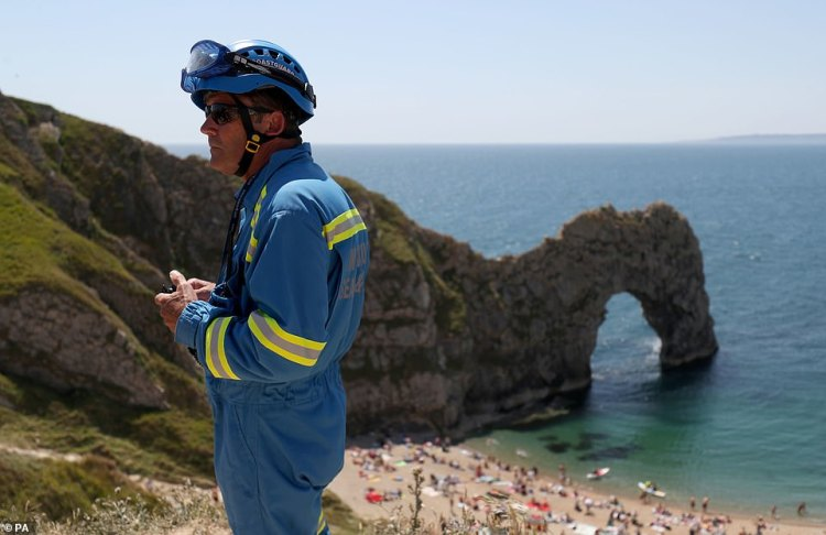 A member of the coastguard looks over a packed beach at Durdle Door, near Lulworth, despite Dorset Council announcing that the beach was closed to the public