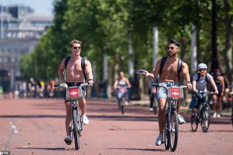 Topless cyclists ride along the Mall in London today as the parks across the city are packed with lockdown-wearing Britons soakin gup the 75F (24C) sun
