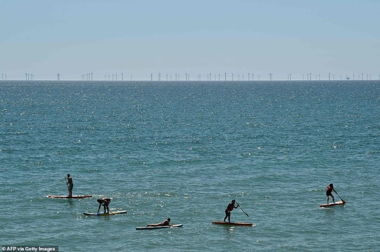 Paddleboarders exercise social-distancing while afloat in the calm sea off Brighton - as thousands cram Britain's beauty spots to soak up the day's 75F (24C) heat