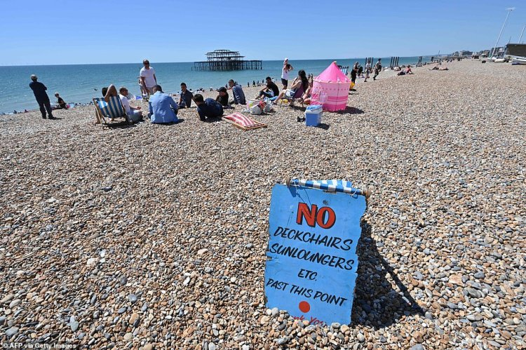 People sunbathe on the beach in front of the derelict West Pier in Brighton, on the south coast of England on May 31, 2020 on the eve of a further relaxation of the novel coronavirus lockdown rules