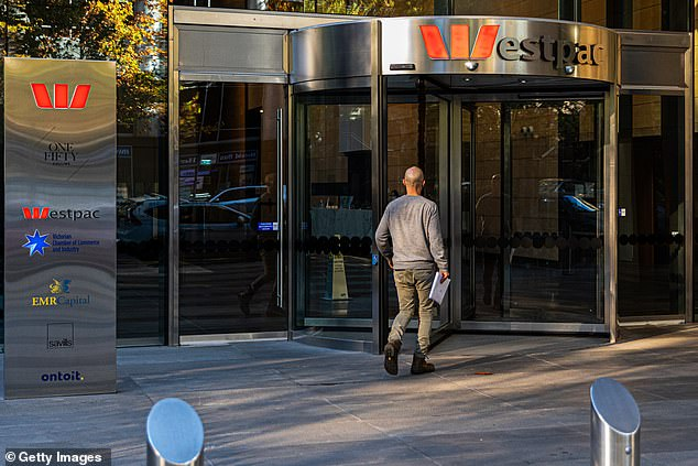 Australia's oldest bank Westpac predicts home borrowers could soon be paid to take out a mortgage or punished for keeping money in the bank. Interest rates in Australia have been at a record-low of 0.25 per cent since March, and are just one cut away from being at zero. Pictured is a Melbourne bank branch on May 13, 2020